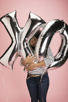 Young woman hugging silver XO balloons against pink background - HEROF32005