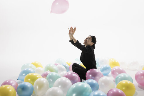 Smiling businesswoman playing with multicolor balloons against white background - HEROF32017