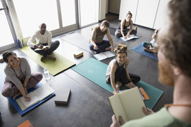 Yoga teacher talking to students with journals on yoga mats in yoga class studio - HEROF32113