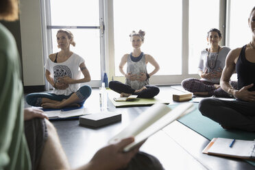 Yoga class with journals practicing breathing with hands on stomachs in yoga class studio - HEROF32116