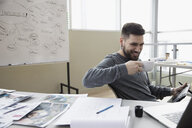 Smiling creative male designer drinking coffee and using graphics tablet in office - HEROF32125