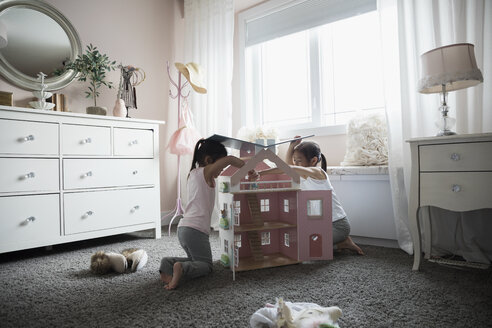 Sisters playing with dollhouse in bedroom - HEROF32137