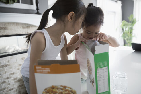 Sisters opening and peering inside cereal box in kitchen - HEROF32140