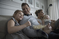Young family watching TV and eating popcorn on living room sofa - HEROF32143