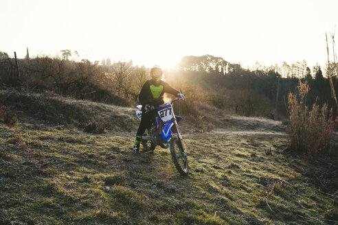 Motocross driver standing on circuit at sunset - FBAF00336