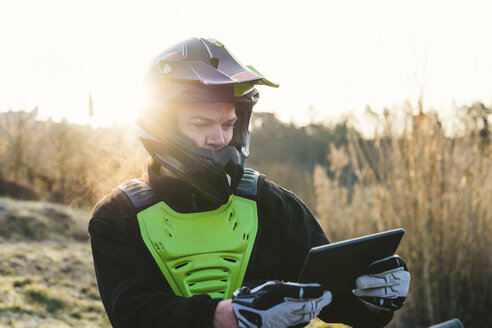 Portrait of motocross driver looking at tablet at sunset - FBAF00339