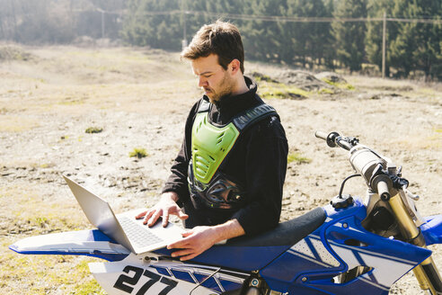 Portrait of motocross driver using laptop - FBAF00351