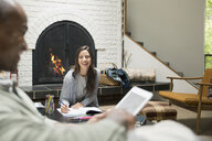Smiling couple reading and writing in living room near fireplace - HEROF32159