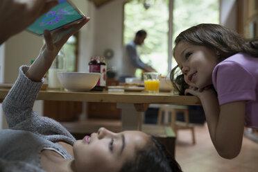 Sisters playing video games on digital tablet at breakfast table - HEROF32168