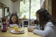 Sisters eating breakfast at kitchen table - HEROF32171