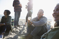 Smiling friends drinking and relaxing at sunny beach picnic - HEROF32198