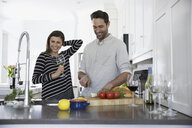 Smiling couple drinking wine and cooking in kitchen - HEROF32246