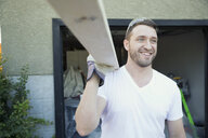 Smiling man carrying wood beam for home improvement project in driveway - HEROF32255
