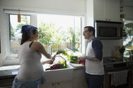 Pregnant couple washing vegetables at kitchen sink - HEROF32258