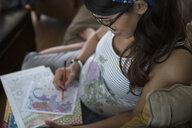 Pregnant woman coloring in adult coloring book - HEROF32264
