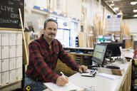 Portrait smiling worker at counter in home improvement store - HEROF32297