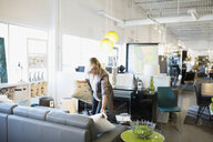 Saleswoman arranging pillows on sofa in home furnishings store - HEROF32300