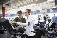 Saleswoman helping woman browsing cardio machines at home gym equipment store - HEROF32309