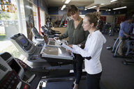 Saleswoman helping woman shopping for treadmill in home gym equipment store - HEROF32312