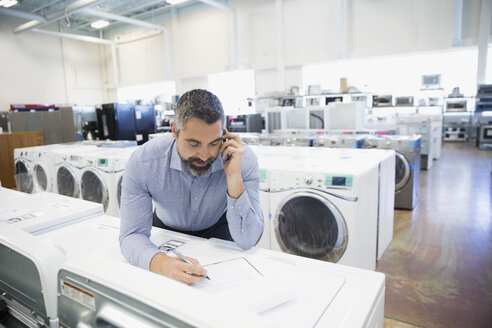 Salesman with clipboard talking on cell phone in appliance store - HEROF32342