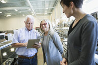 Saleswoman helping senior couple with digital tablet in appliance store - HEROF32345
