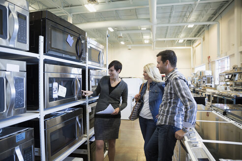 Saleswoman helping couple shopping for microwave in appliance store - HEROF32351