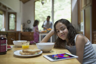 Portrait smiling girl with digital tablet eating breakfast at kitchen table - HEROF32366