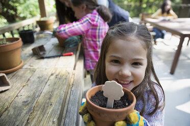 Portrait smiling girl holding flowerpot - HEROF32369