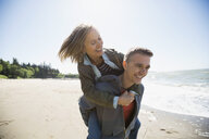 Playful couple piggybacking on sunny beach - HEROF32402