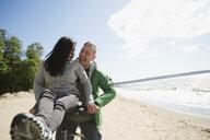 Playful couple riding bicycle on sunny beach - HEROF32408