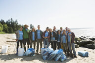 Portrait smiling beach cleanup volunteers on sunny beach - HEROF32411
