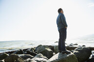 Pensive man looking at ocean view on sunny beach rocks - HEROF32414