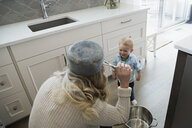 Playful mother and baby son playing with pots in kitchen - HEROF32426