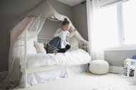 Playful girl jumping off bed - HEROF32429