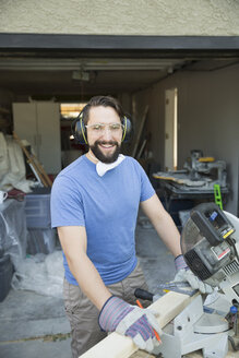 Portrait smiling man doing home improvement project at table saw in driveway - HEROF32432
