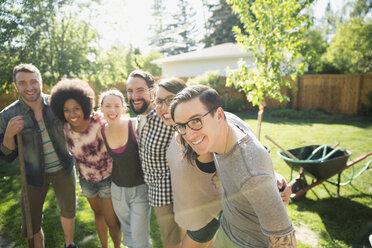 Portrait smiling friends planting tree in sunny backyard - HEROF32435