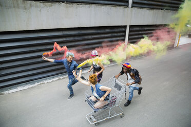 Playful young friends with shopping cart and color powder cannons on urban street - HEROF32456