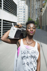 Portrait cool young woman with retro boom box in sunny urban alley - HEROF32480