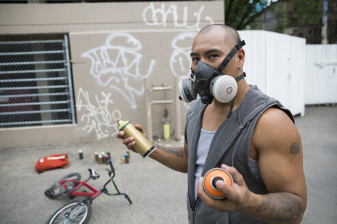 Portrait graffiti artist wearing protective mask with spray paint in urban alley - HEROF32510