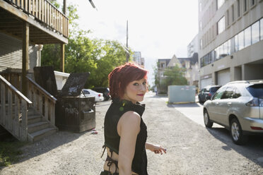 Portrait cool woman with red hair looking over shoulder in urban alley - HEROF32519