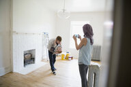 Mother photographing playful father holding son in empty new house - HEROF32540