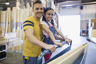 Portrait smiling father and daughter with wood planks at home improvement store - HEROF32543