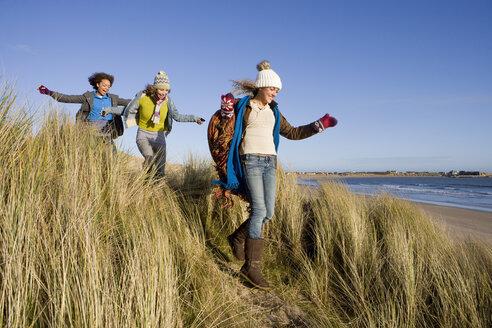 Friends walking on sand dune near beach - JUIF00608