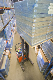 Warehouse worker moving boxes on forklift - JUIF00617