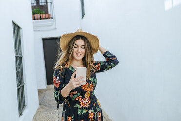 Spain, Cadiz, Vejer de la Frontera, fashionable woman looking at mobile phone - KIJF02445
