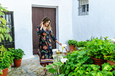 Spain, Cadiz, Vejer de la Frontera, fashionable woman looking at Callas at patio - KIJF02454