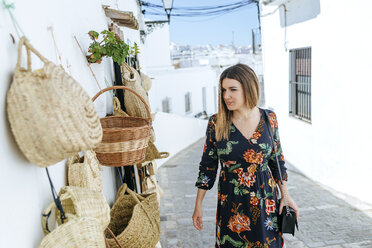 Spain, Cadiz, Vejer de la Frontera, fashionable woman looking at bags and baskets at a shop - KIJF02457
