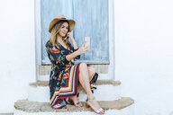Spain, Cadiz, Vejer de la Frontera, fashionable woman taking selfie with mobile phone in front of blue door - KIJF02460