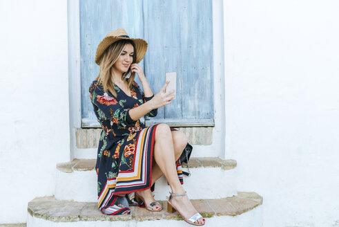 Spain, Cadiz, Vejer de la Frontera, fashionable woman taking selfie with mobile phone in front of blue door - KIJF02460