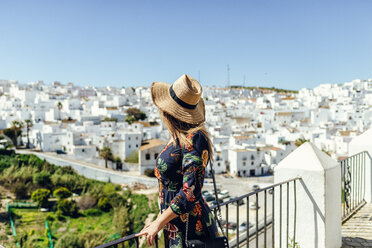 Spain, Cadiz, Vejer de la Frontera, fashionable woman standing on roof terrace looking at view - KIJF02463